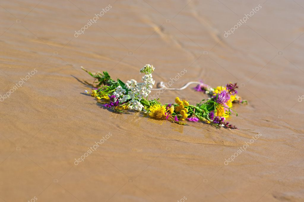 Circlet of flowers on a sandy beach — Stock Photo #8976433