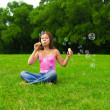 Girl blowing soap bubbles — Stockfoto