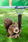 Garden decoration,squirrel with lamp and cone — Stock Photo