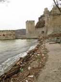 The old castle ruins and rubbish on the river bank — Stock Photo