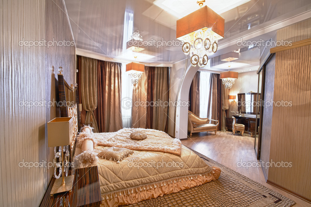 Interior of a beautiful bedroom with a queen size bed and designer lamps  Stock Photo #10697490