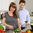 Stock Photo: Young couple preparing salad