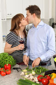 Young couple kissing in their kitchen — Stock Photo