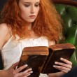 Royalty-Free Stock Photo: Beautiful redhead reading a bible