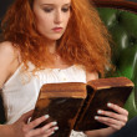 Beautiful redhead reading a bible — Stock Photo