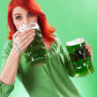 Redhead enjoying green beer — Stock Photo