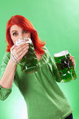 Redhead enjoying green beer — Stockfoto