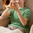 Playing the trumpet at home — Stock Photo