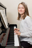 Happy young girl playing the piano — Stock Photo