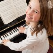 Stock Photo: Smiling girl playing her piano