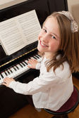 Smiling girl playing her piano — Stock Photo