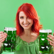 Redhead holding green beers — Stock Photo