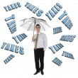 Taxes word and business man with umbrella — Stock Photo