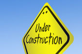 Under construction word on road sign — Stock Photo
