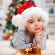 Little Christmas boy with Christmas present — Stock Photo