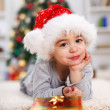 Little Christmas boy with Christmas present - Stock Photo