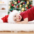 Cute boy laying in front of Chrismas tree — Stock Photo