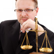 Serious attorney with golden scale — Stock Photo