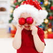 Photo: Boy holding Christmas decoration in front of eyes
