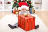 Little boy sitting behind big present — Stockfoto