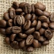 Cofee beans on burlap — Stock Photo