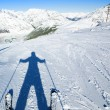 Stock Photo: Shadow of ready to go downhill skier