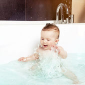 Cute baby having fun, splashing water and laughing while taking a bath in a modern bathroom interior — Stock Photo