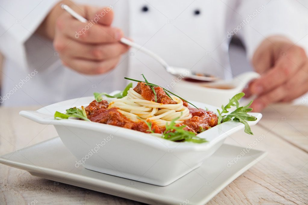 Male chef in restaurant kitchen is garnishing and preparing pasta dish  Stock Photo #10451671