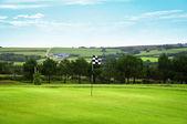 гольф зеленый с клетчатым флагом - сельской местности в фоновом режиме — Стоковое фото