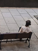 Beggar sitted on a bench — Stock Photo