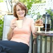 Stock Photo: Woman in backyard with coffee and cookies