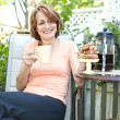 Royalty-Free Stock Photo: Woman in backyard with coffee and cookies
