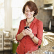 Woman using cell phone at home - Stock Photo