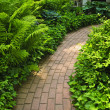 Brick path in landscaped garden - Stock Photo