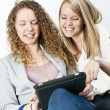 Two women using tablet computer — Stock Photo