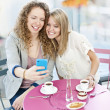 Woman showing phone to friend — Stockfoto