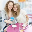Stock Photo: Woman showing phone to friend