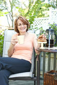 Woman in backyard with coffee and cookies — Stock Photo