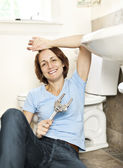 Woman fixing plumbing — Stockfoto
