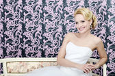 Bride smiling sitting bench — Stock Photo