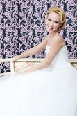 Smiling bride put out her toungue sitting bench — Stock Photo