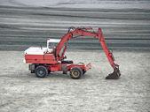 Máquina excavadora estacionada sobre la arena — Foto de Stock