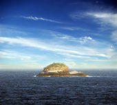 Lonely island on the sea under beautiful blue sky and clouds — Stock Photo