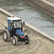 Blue grader tractor waiting to clean the beach sand — Stock Photo