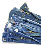 Pile of blue jeans over white background — Stock Photo