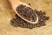 Black pepper from a wooden spoon — Stock Photo