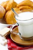 Färsk mjölk i kannan och koppen och croissant — Stockfoto