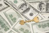 Golden key on money background — Stock Photo