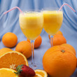 Two crystal glasses of fresh orange juice with oranges and straw — Stock Photo