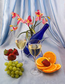 Glasses of wine with fruit and orchid — Stock Photo